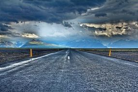 bright photo of a highway against a stormy sky