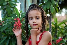 girl on a background of a plant with small red flowers