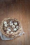 top view of quail eggs in a basket on a wooden surface