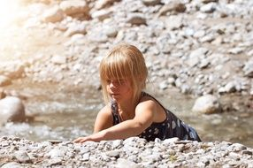 Girl iterates over stones in a mountain stream