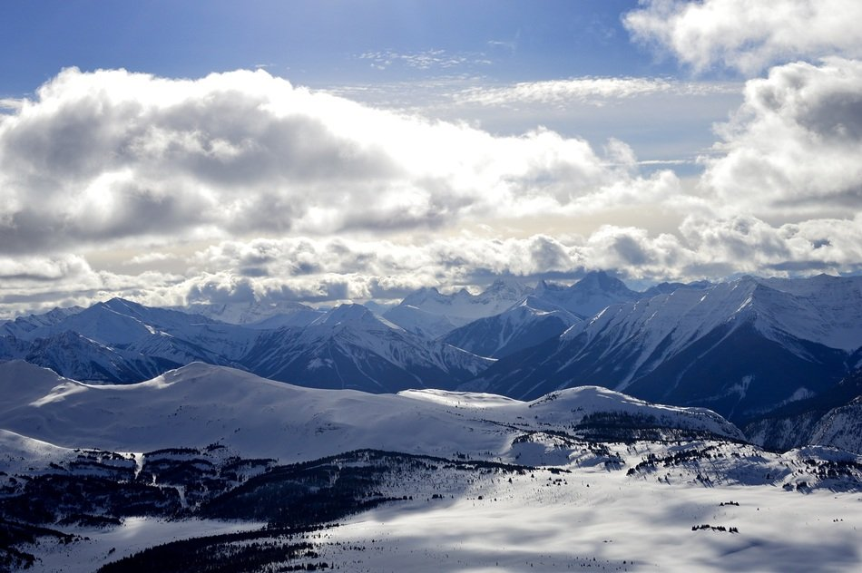 clouds over snowy rocky mountains in alberta