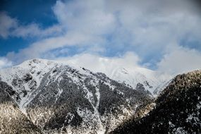 panorama of snowy peaks of mountains and clouds