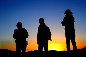 silhouette of travelers on sunset background