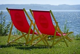 red sun loungers on the shore near the lake