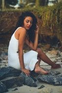 girl in a white dress sitting on a stone