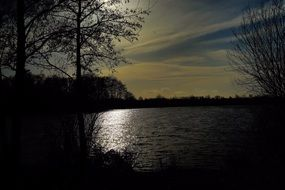 reflection of the evening sun in a dark lake