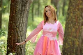young woman in pink dress in the forest