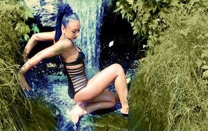 model in sexy swimsuit in the waterfall