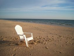 white garden chair on the beach