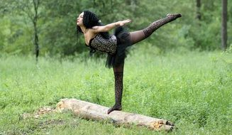 girl in a black ballet dress rehearsing a dance in nature