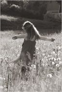 black and white photo of a girl among meadow flowers