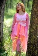 woman in fairy pink dress in the forest