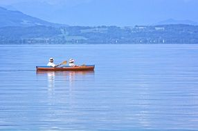 man and woman in Rowing Boat on water in view of green mountain coastline