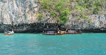 wooden boats off the rocky coast of phi phi island
