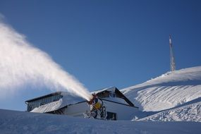 snow cannon on a ski slope on a sunny day