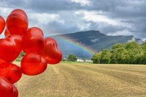 red balloons above Field in view of Rainbow at mountain