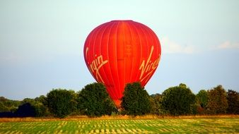 Red hot Air Balloon at harvested field
