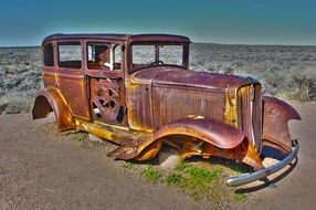 rusty antique american car on the side of highway 66