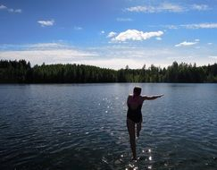 girl with a run jumps into the Finnish lake
