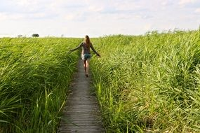 girl on a wooden path among tall green grass