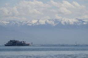 ship on Lake Constance amid snow-capped mountains