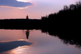 reflection of a purple sunset in a lake in Quebec Canada