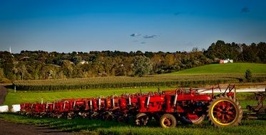 row of antique red tractors on a farm