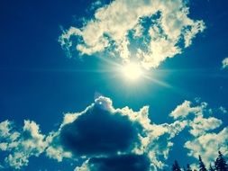 Sun shines among clouds in blue Sky