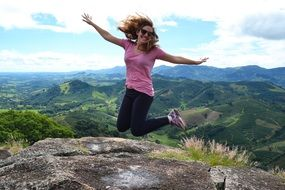 photo of a jumping girl on top of a mountain