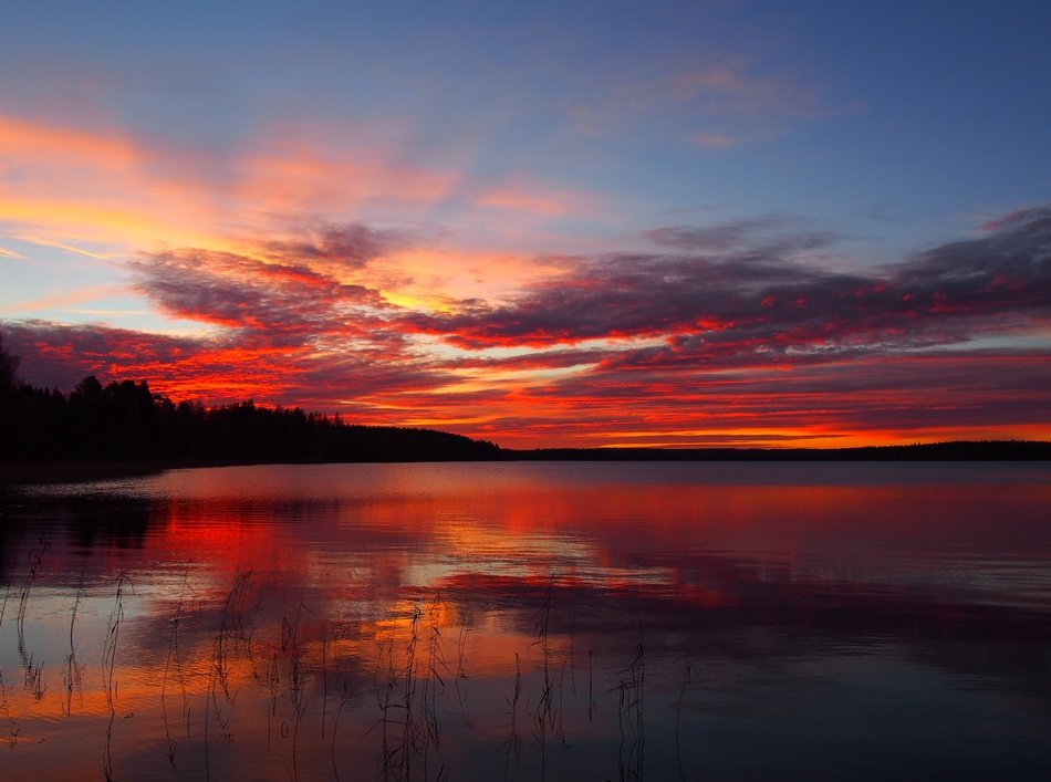 red sunset in the clouds over a lake in finland