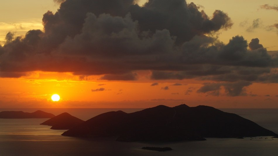 gorgeous Sunset with dark clouds above rocky islands at calm sea, British Virgin Islands