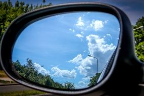 white clouds reflected in the side rearview mirror