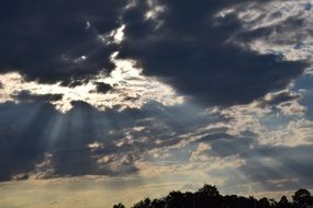 bright sunbeams through dark clouds