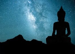silhouette of a large Buddha statue on the background of the Milky Way