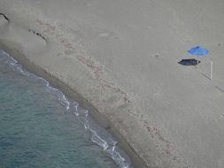 lonely blue umbrella on a sandy beach