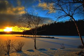 distant view of yellow sunset over a snowy lake in Quebec
