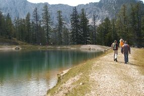 people Hiking on lake coast at mountains, austria