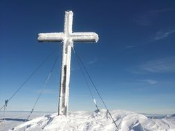 Cross on the summit of the mountain in the winter