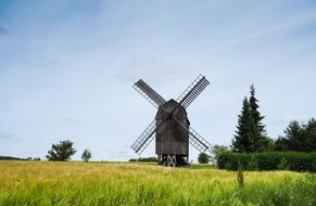 wooden Windmill in field on a sunny day