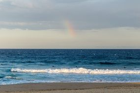 distant view of a rainbow over a beach in New South Wales