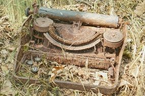 rotting typewriter in dry grass