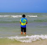young man in a yellow-blue t-shirt is fishing in the ocean