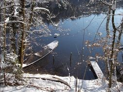 lake with a boat in the winter forest