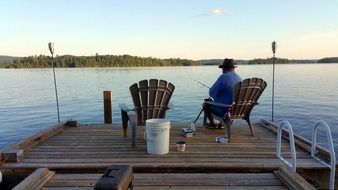fisherman in a beach chair on a wooden pier