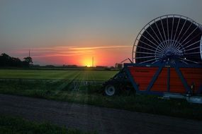 agricultural field irrigation machine at sunset
