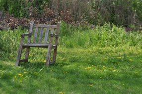 wooden old chair on green grass in the meadow