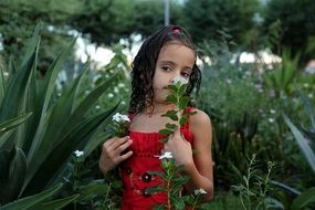 little girl with a flower in the thickets of the garden