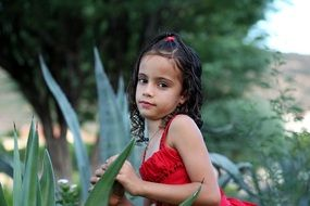 little girl in a red dress at a photo shoot in the garden