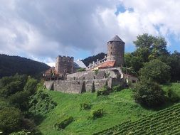 castle on a green hill on a background of white clouds