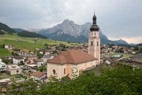 panorama of a village with a church in the mountains of south tyrol